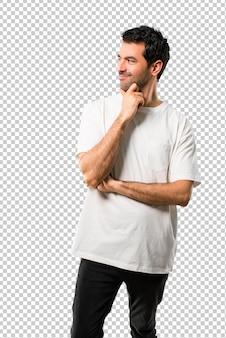 Junger mann mit dem weißen hemd, das zur seite mit der hand auf dem kinn steht und schaut