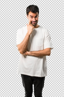 Junger mann mit dem weißen hemd, das zur vorderen öffnung das auge mit dem finger steht und schaut