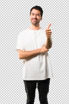 Junger mann mit dem weißen hemdgeben daumen herauf geste