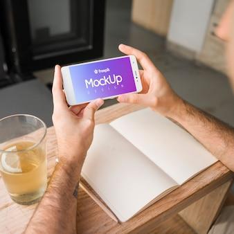 Junger mann mit einem smartphonemodell