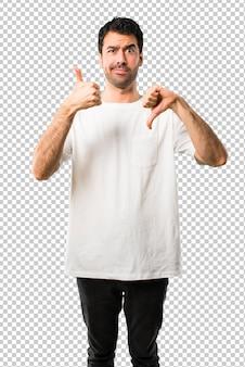 Junger mann mit weißem hemd, das gut-schlechtes zeichen macht. unentschlossene person zwischen ja oder nein