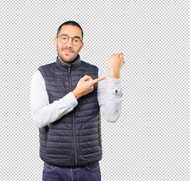 Junger mann zeigt auf sein handgelenk