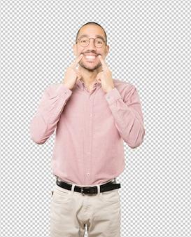Junger mann zeigt auf seine zähne
