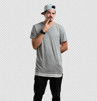 Junger rapper, der zweifelt und verwirrt, an eine idee denkt oder sich um etwas sorgt