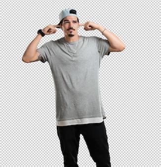 Junger rapper mann, der ohren mit händen bedeckt, wütend und müde, etwas geräusch zu hören