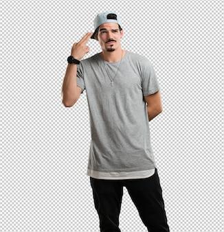 Junger rappermann, der eine selbstmordgeste macht, eine gewehr mit den fingern bildend traurig und erschrocken sich fühlt