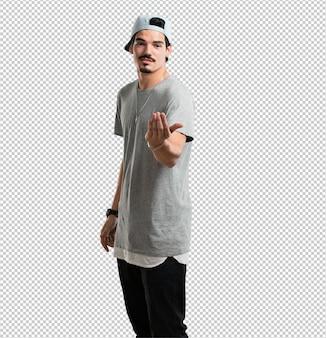 Junger rappermann, der einlädt zu kommen, zuversichtlich und lächelnd, eine geste mit der hand machend, positiv und freundlich seiend