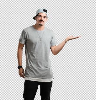 Junger rappermann, der etwas mit den händen hält, ein produkt zeigt, und fröhlich lächelt und einen eingebildeten gegenstand anbietet
