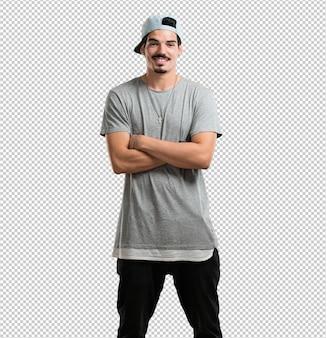 Junger rappermann, der seine arme kreuzt, lächelt und glücklich, ist überzeugt und freundlich