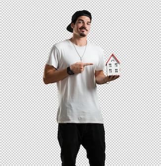 Junger rappermann glücklich und überzeugt, ein miniaturhausmodell zeigend