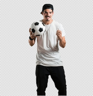 Junger rappermann lächelnd und glücklich, einen fußball halten, wettbewerbsfähige haltung, aufgeregt, um ein spiel zu spielen
