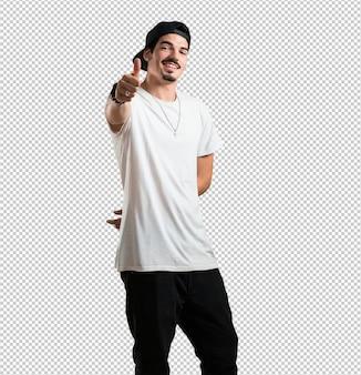 Junger rappermann nett und aufgeregt, ihren daumen, konzept des erfolgs und zustimmung, okaygeste oben lächelnd und anheben