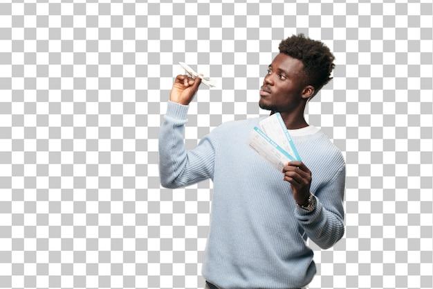 Junger schwarzer mann mit bordkartenkarten und einem flugzeugmodell. reisekonzept