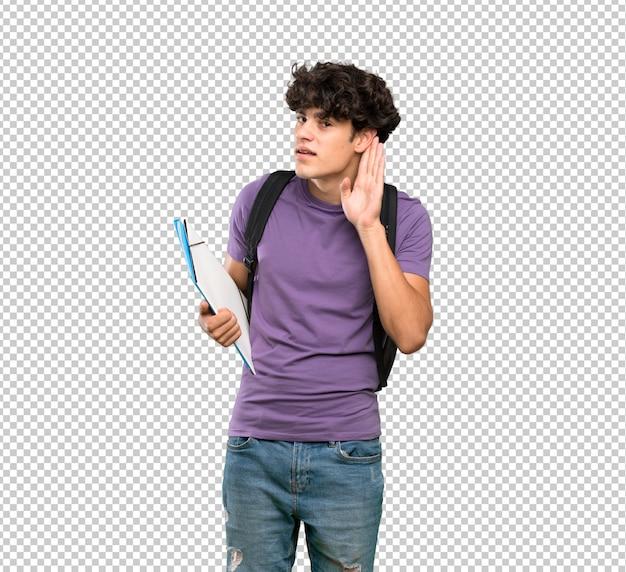 Junger studentenmann, der auf etwas hört, indem er hand auf das ohr setzt