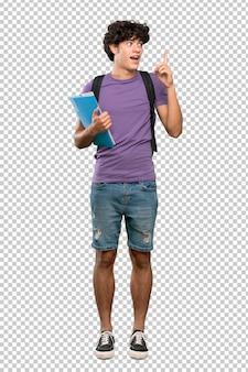 Junger studentenmann, der beabsichtigt, die lösung beim anheben eines fingers zu verwirklichen
