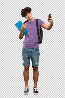 Junger studentenmann, der ein selfie macht