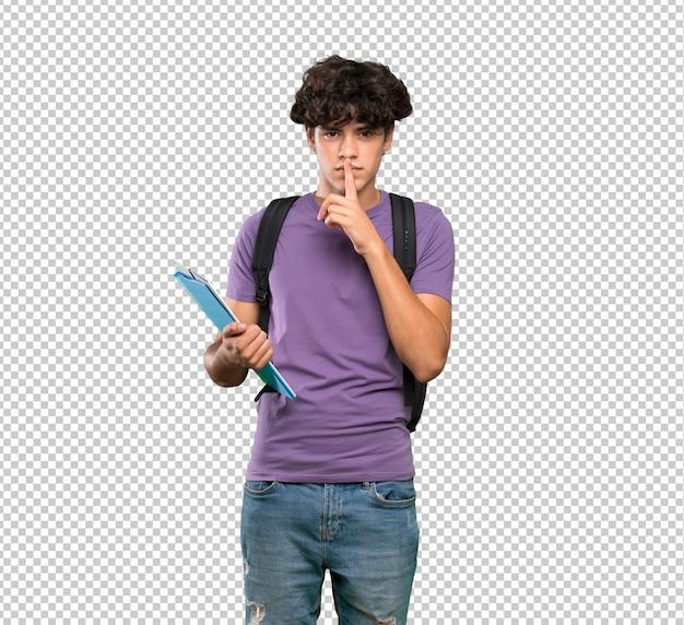 Junger studentenmann, der ein zeichen der ruhegeste einsetzt finger in mund zeigt