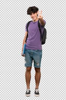 Junger studentenmann, der siegeszeichen lächelt und zeigt