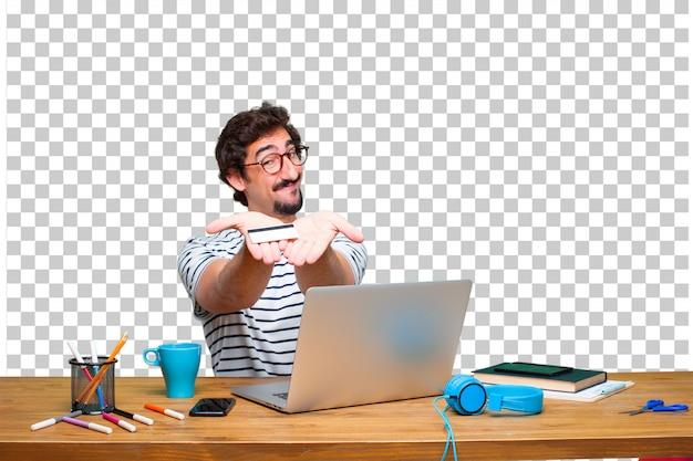 Junger verrückter grafikdesigner auf einem schreibtisch mit einem laptop und lohn-, kauf- oder geldkonzept
