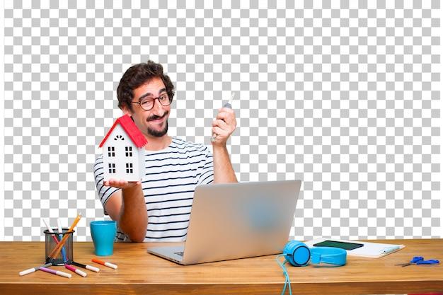 Junger verrückter grafikdesigner auf einem schreibtisch mit einem laptop und mit einem hausmodell