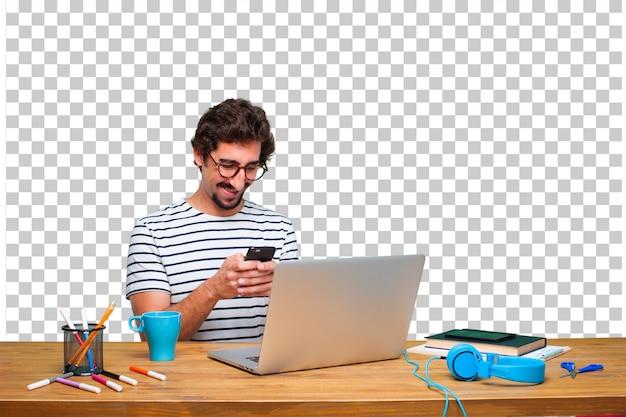 Junger verrückter grafikdesigner auf einem schreibtisch mit einem laptop und mit einem intelligenten touch screen telefon