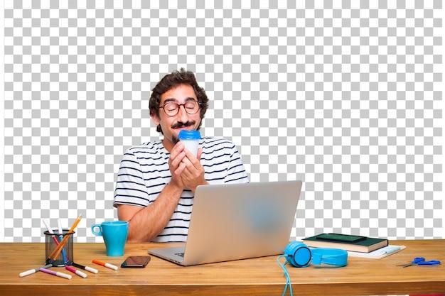 Junger verrückter grafikdesigner auf einem schreibtisch mit einem laptop und mit einem kaffee zum mitnehmen