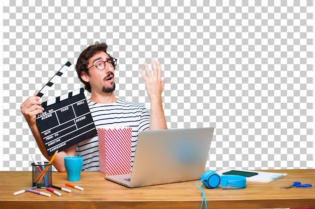 Junger verrückter grafikdesigner auf einem schreibtisch mit einem laptop und mit einem kino-scharnierventil