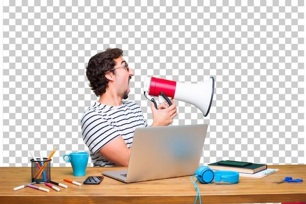 Junger verrückter grafikdesigner auf einem schreibtisch mit einem laptop und mit einem megaphon