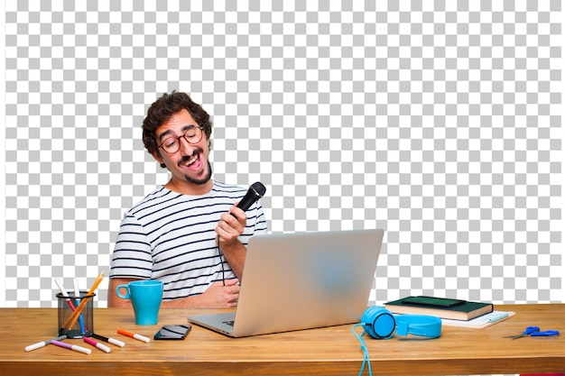 Junger verrückter grafikdesigner auf einem schreibtisch mit einem laptop und mit einem mikrofon