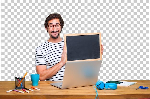 Junger verrückter grafikdesigner auf einem schreibtisch mit einem laptop und mit einem plakat