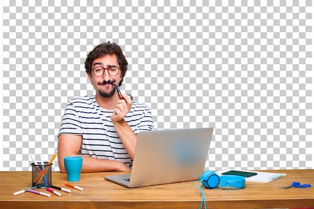 Junger verrückter grafikdesigner auf einem schreibtisch mit einem laptop und mit einem rauchweinleserohr