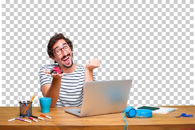 Junger verrückter grafikdesigner auf einem schreibtisch mit einem laptop und mit einem roten automodell