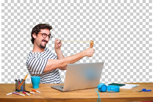 Junger verrückter grafikdesigner auf einem schreibtisch mit einem laptop und mit einem slingshot