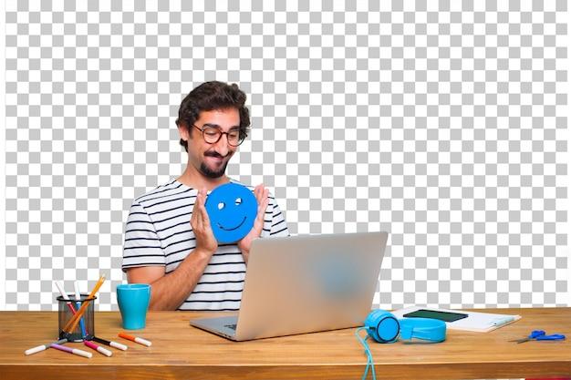 Junger verrückter grafikdesigner auf einem schreibtisch mit einem laptop und mit einem smiley emoticon