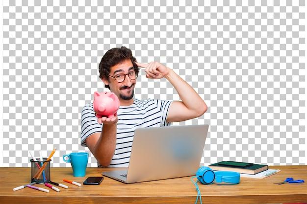 Junger verrückter grafikdesigner auf einem schreibtisch mit einem laptop und mit einem sparschwein