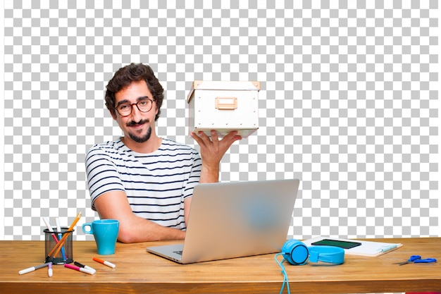 Junger verrückter grafikdesigner auf einem schreibtisch mit einem laptop und mit einem weinlesekasten