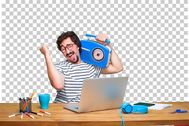 Junger verrückter grafikdesigner auf einem schreibtisch mit einem laptop und mit einem weinleseradio