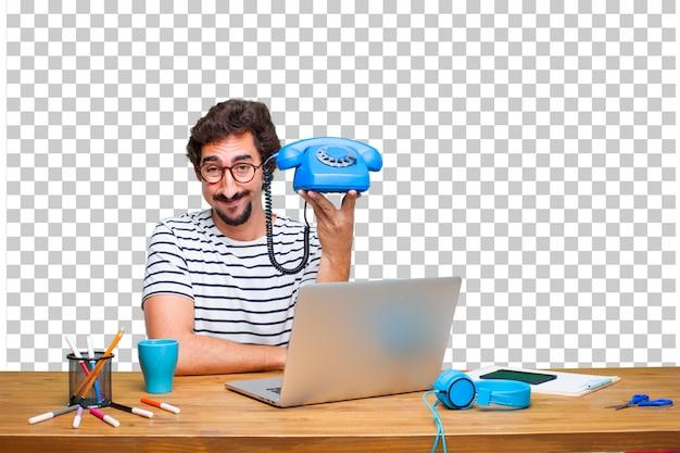 Junger verrückter grafikdesigner auf einem schreibtisch mit einem laptop und mit einem weinlesetelefon