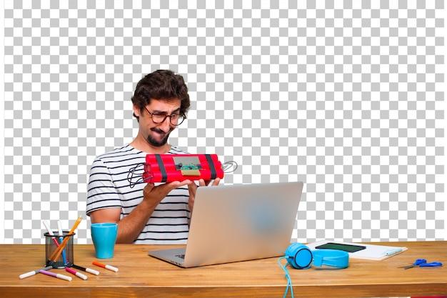 Junger verrückter grafikdesigner auf einem schreibtisch mit einem laptop und mit einer dynamitbombe