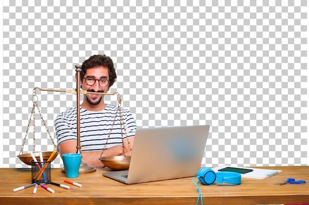Junger verrückter grafikdesigner auf einem schreibtisch mit einem laptop und mit einer gerechtigkeitsbalance oder -skala