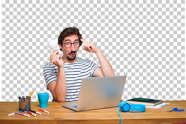 Junger verrückter grafikdesigner auf einem schreibtisch mit einem laptop und mit einer glühlampe. idee konzept