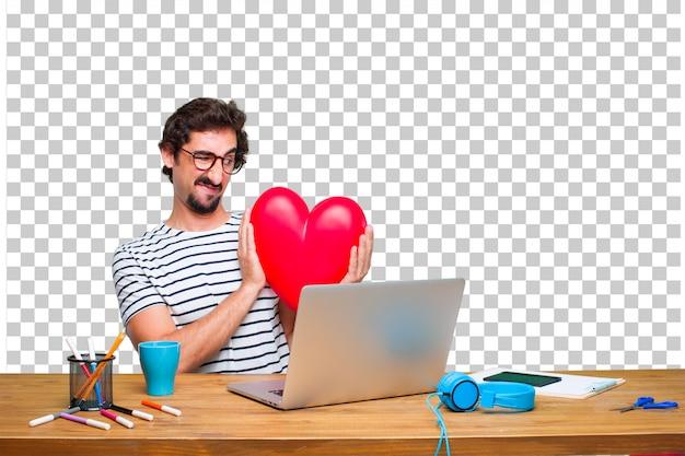 Junger verrückter grafikdesigner auf einem schreibtisch mit einem laptop und mit einer herzform. liebe konzept