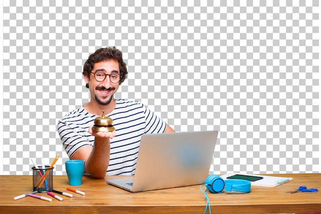 Junger verrückter grafikdesigner auf einem schreibtisch mit einem laptop und mit einer klingelglocke