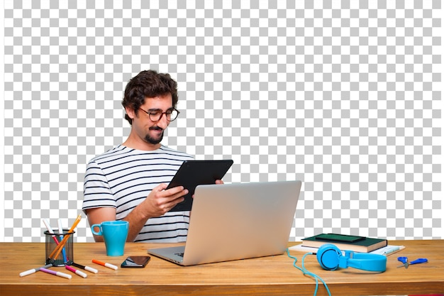 Junger verrückter grafikdesigner auf einem schreibtisch mit einem laptop und mit einer touch screen tablette