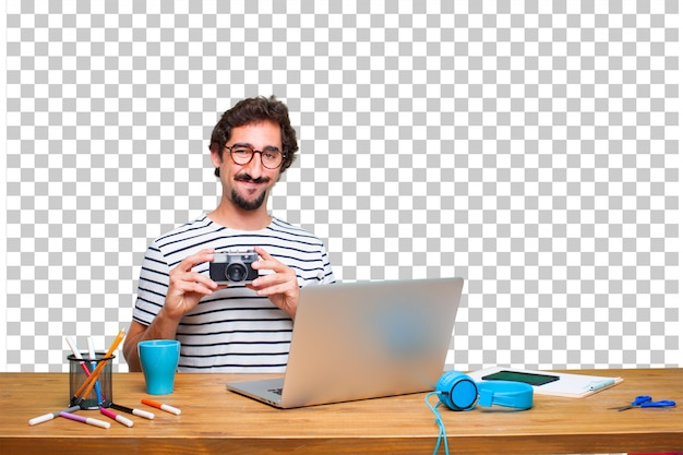 Junger verrückter grafikdesigner auf einem schreibtisch mit einem laptop und mit einer weinlesekamera