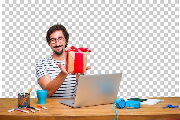 Junger verrückter grafikdesigner auf einem schreibtisch mit einem laptop und mit geschenkboxkonzept