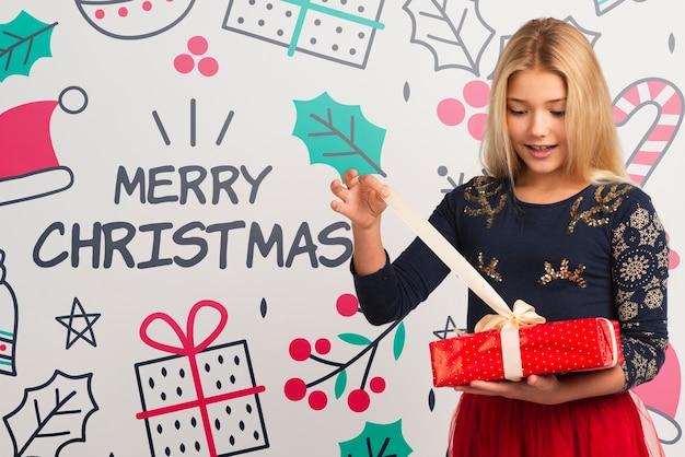 Junges mädchen, das geschenk auf weihnachten auspackt