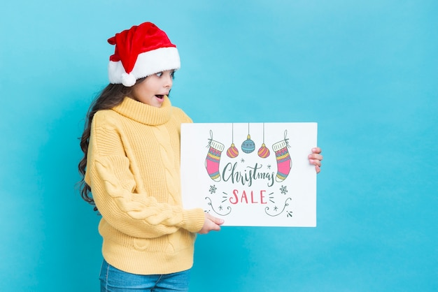 Junges mädchen, das weihnachtsverkaufsanzeige überrascht betrachtet