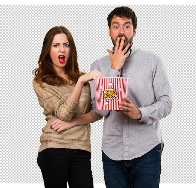 Junges paar, das popcorn isst