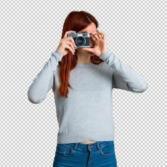 Junges rothaarigemädchen, das eine kamera hält